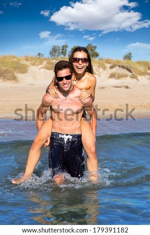 Teen couple running piggyback on summer beach splashing water - stock photo