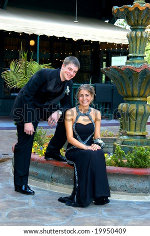 Teen couple sit outdoors at a water fountain dressed and ready for prom night.  Tux and gown both in black. - stock photo