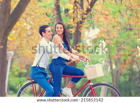 Teen couple with bike in the park in autumn time - stock photo