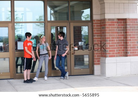teen girl and guys outside school smiling