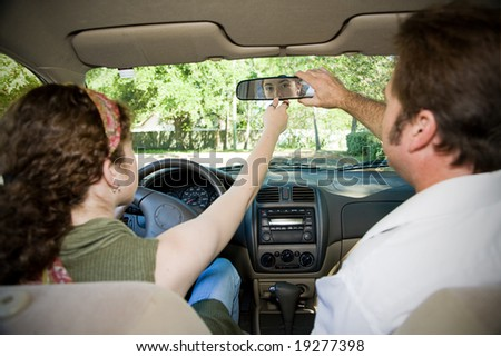Teen girl and her driving instructor adjusting rearview mirror.  Focus on girl in the mirror. - stock photo
