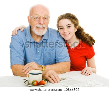 Teen girl and her grandfather at the table filling out paperwork together.  Isolated on white. - stock photo