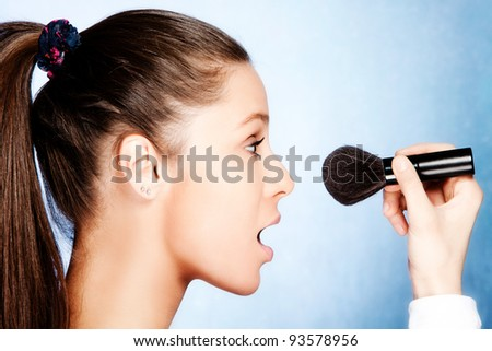 teen girl  apply powder with cosmetic brush, profile, studio shot - stock photo