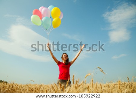 Teen girl at a wheat field with balloons - stock photo