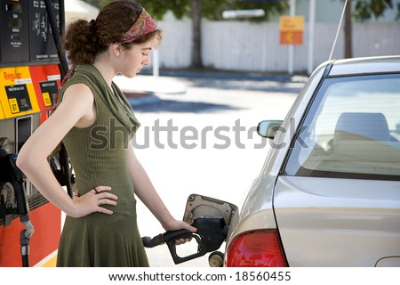 Teen girl at the gas station filling up the fuel tank in her gas efficient car.