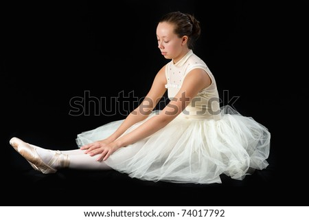 teen girl ballet dancer sitting in a tutu in points on a black background - stock photo