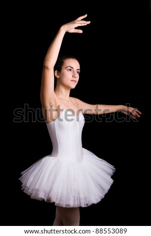 Teen girl ballet dancer standing in a tutu on a black background - stock photo