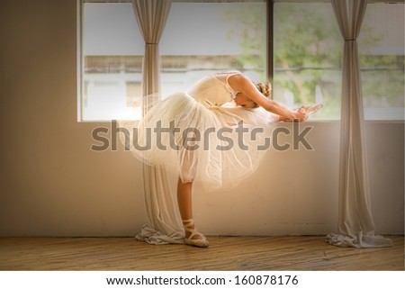 teen girl ballet dancer stretching beside a window - stock photo
