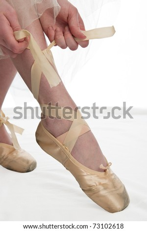 teen girl ballet dancer tying shoe