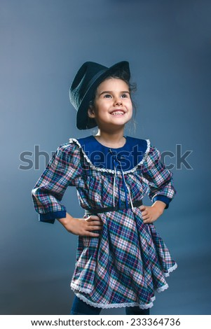 Teen girl child in a plaid dress and men's hat looking to the side on a gray background