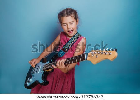 Teen girl child seven years, European appearance brunette in a pink dress plays a guitar and sings his eyes closed on a gray background, music, song - stock photo