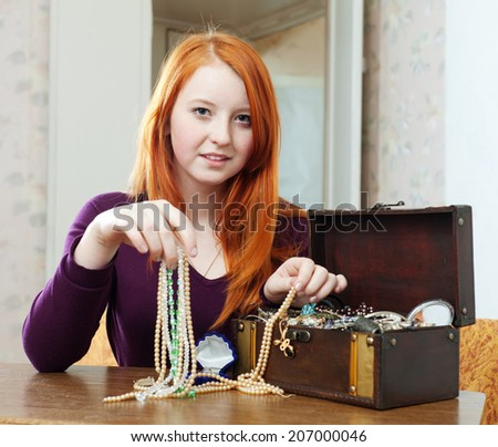 teen girl chooses jewelry in treasure chest at home  - stock photo