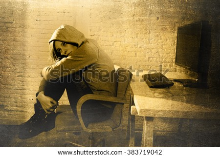 teen girl cyber abused suffering internet cyberbullying scared and desperate in fear face expression sitting back to computer monitor in  bullying social problem edgy grunge lighting - stock photo