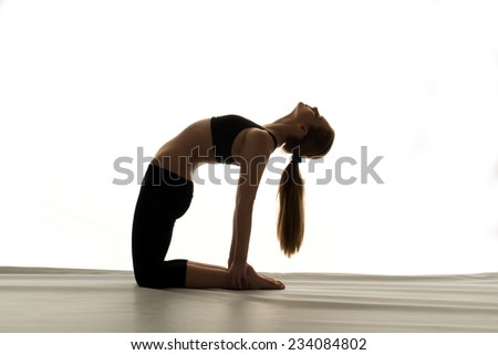 Teen girl doing a yoga stretch in silhouette.   - stock photo