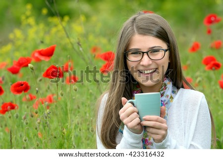 Teen girl drink cup of tea on poppy field - stock photo
