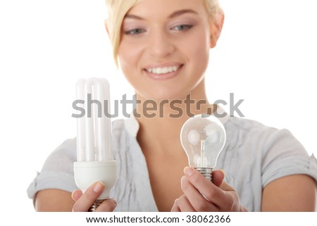 Teen girl environmentalist comparing one compact fluorescent light bulb to incandescent light bulb
