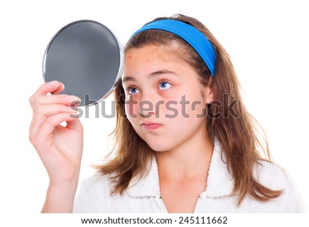 Teen girl examine her pimples in the mirror - stock photo