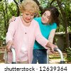 Teen girl helping a senior lady with a walker. - stock photo