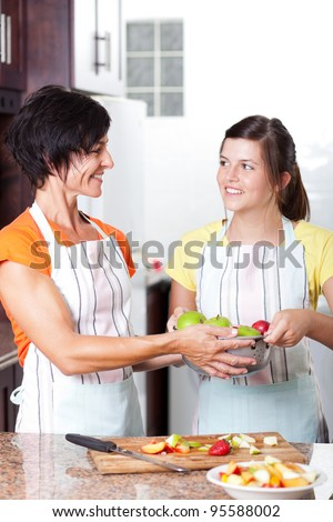 teen girl helping mother in home kitchen - stock photo