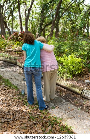 Teen girl helping senior woman walk through the park.  Vertical view with room for text. - stock photo