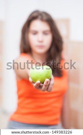 teen Girl holding a beautiful, fresh green apple indoor, selective focus on apple.Pretty teen girl concentrated  hold green fresh apple in hand.. girl holding an green apple, healthy eating - stock photo