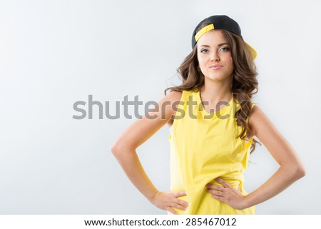 Teen girl in a cap backwards and yellow T-shirt on a white background - stock photo