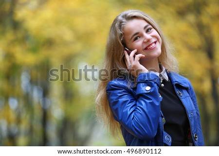 Teen girl in autumn park with mobile phone