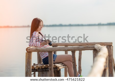teen girl in long t-shirt sit on the bridge with her camera.