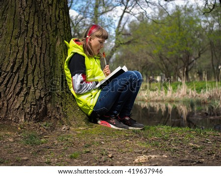 Teen girl in the park with a book. Concept - exam preparation, difficulty learning, school. The girl has her hair dyed red. Bright jacket. Teen girl in the park with a book.