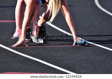 Teen Girl in the Starting Blocks at a Track Meet - stock photo