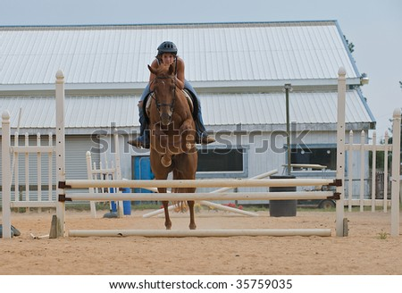 Teen girl jumping a horse over rails. - stock photo