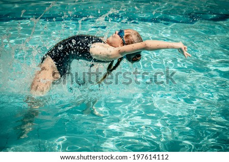 teen girl jumping in the swimming pool at the day time - stock photo