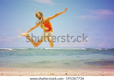 teen girl  jumping on the beach at blue sea shore in summer vacation at the day time