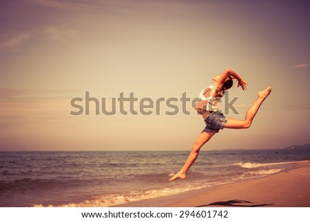 Teen  girl  jumping on the beach at the day time