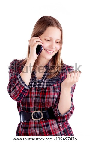 Teen girl laughing and talking on the phone, studio shot - stock photo