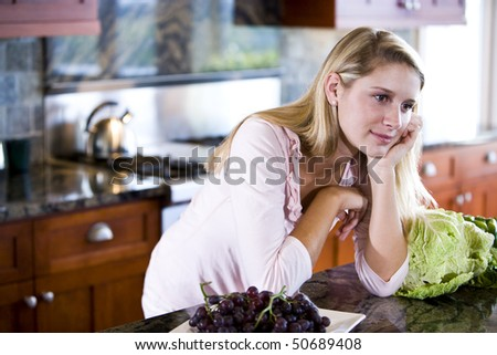 Teen girl leaning on kitchen counter daydreaming - stock photo