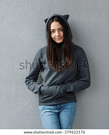Teen girl leans against a wall - stock photo
