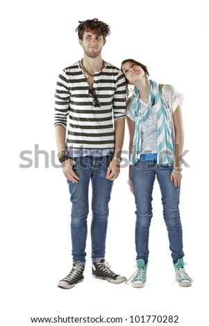 Teen girl leans head on shoulder of teen boy, smiles and looks up at him. Vertical, isolated on white, copy space.