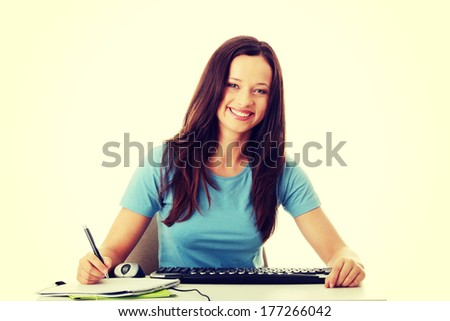 Teen girl learning at the desk (e-learning concept), isolated on white   - stock photo