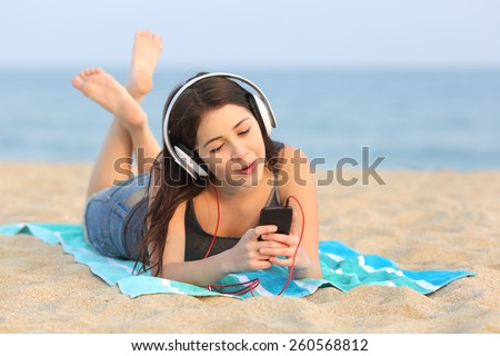 Teen girl listening to the music from a smart phone and singing lying on the sand of the beach - stock photo