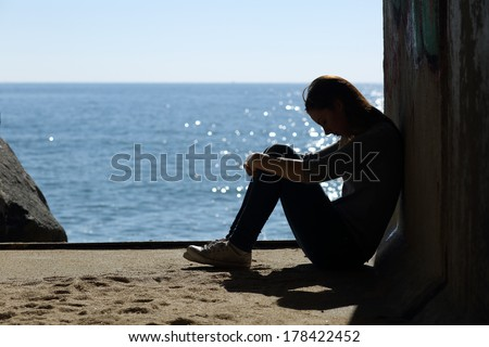 Teen girl lonely and sadness on the beach with the sea in the background - stock photo