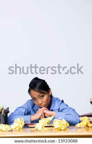Teen girl looking sad and frustrated as she sits at a desk surrounded by crumpled paper, pens, pencils, and folders. Vertically framed photograph - stock photo