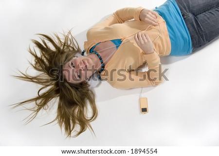teen girl lying on floor listening to music - stock photo
