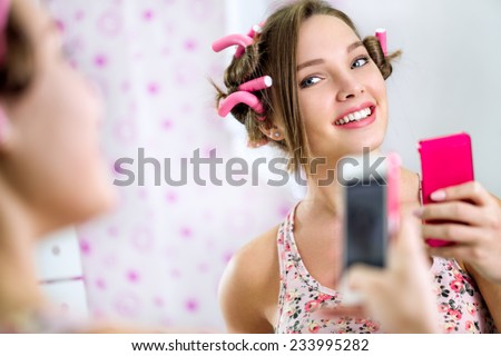 Teen girl making self in bathroom  front mirror - stock photo