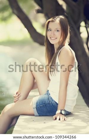 Teen girl near lake in the park. - stock photo