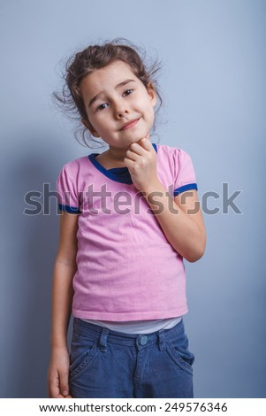 Teen girl of European appearance, brunette cheek propped his fist on a gray background, nice smile - stock photo
