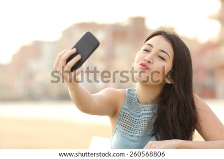 Teen girl photographing a selfie kissing camera with a smart phone in an urban park - stock photo