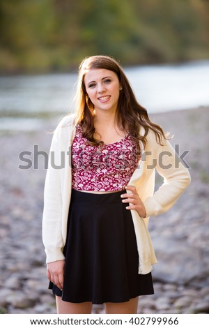 Teen girl poses for a high school senior portrait photo outdoors near a river in Eugene Oregon. - stock photo