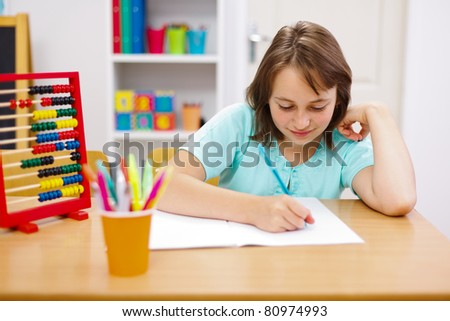 Teen girl practicing and doing homework alone in classroom