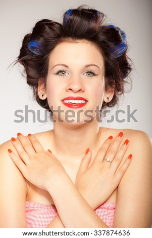 Teen girl preparing to party. Portrait of young woman with hair curlers pin up makeup red lips and nails studio shot on gray. Hairstyle and manicure.
